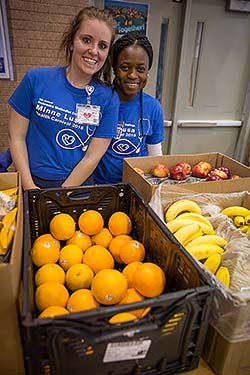 NMC nursing students with fruit available at the Minne Lusa Health Carnival.