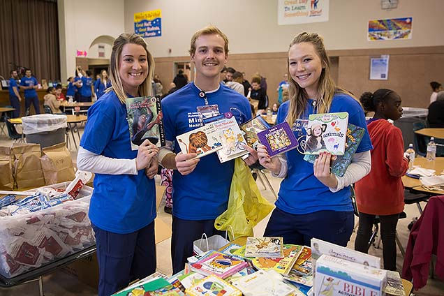 NMC nursing students with some of the free children's books available at the Minne Lusa Health Carnival.