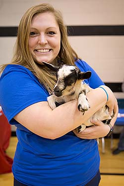 NMC nursing student holds baby goat at the Minne Lusa Health Carnival.