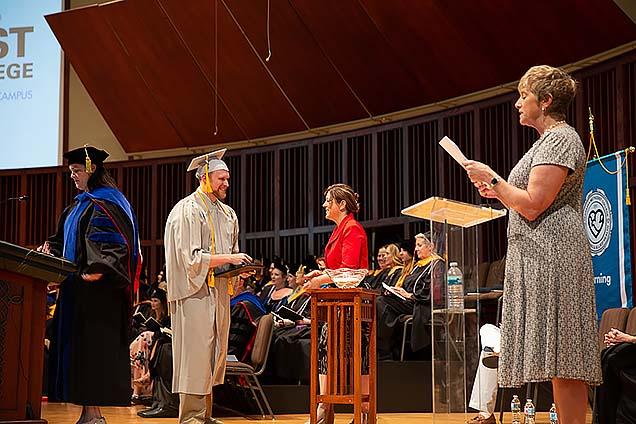 A student receives his diploma at graduation.