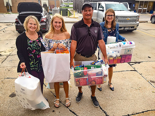 Megan Jacobsen, her parents, and Director of Student Support Services Lisa Johnson bring the items from Megan's food drive into the NMC Food Pantry.