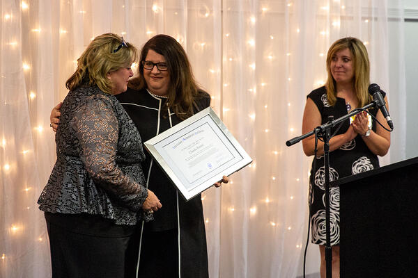 Stephanie Pettett receives honorary diploma in Cheyla's name from Michelle Massey, with Angela Heesacker Smith at right.