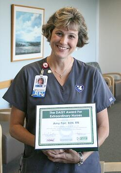 Amy Parr holds her DAISY Award certificate for excellence in nursing.