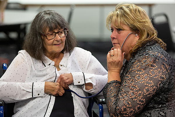 Heart recipient Jan Going positions stethoscope so Stephanie Pettett can listen to Cheyla's heart beating.