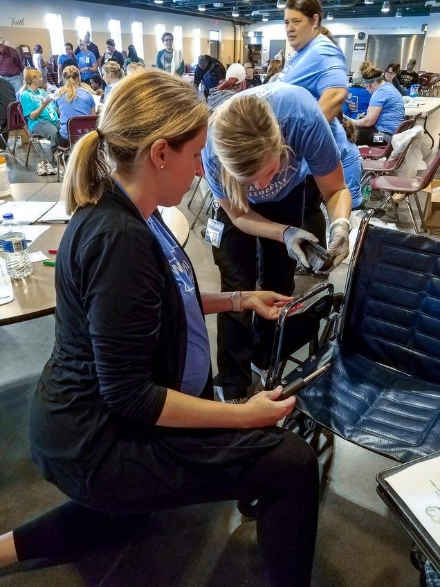 MOT Program Director Melissa Kimmerling, EdD, OTR/L, and student Erin Shuck make wheelchair adjustments.