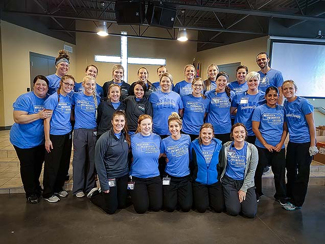 MOT Academic Fieldwork Coordinator Michelle Massey, MS, OTR/L (2nd row, far left), with MOT students. at the Foot Care Clinic for the Homeless.