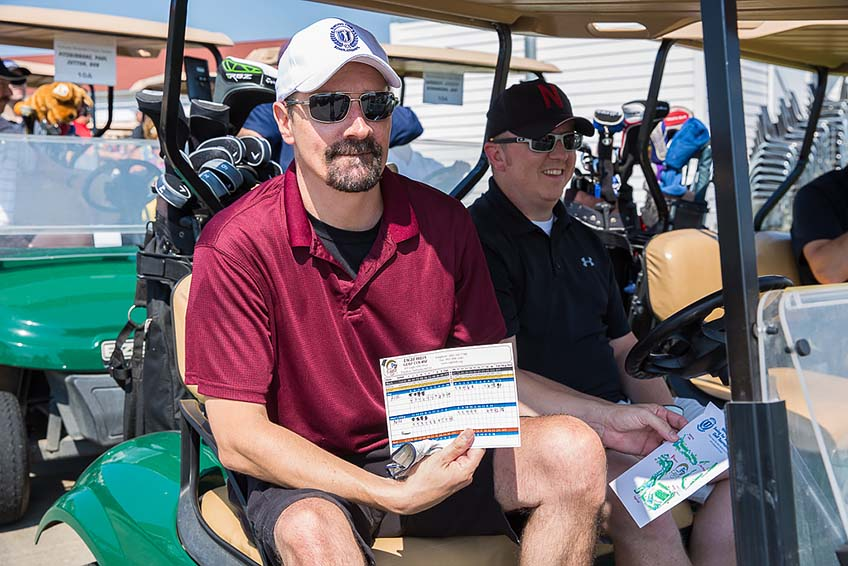 Matt Stockfeld in sunglasses and a hat, sitting in a golf cart, holding up his score card