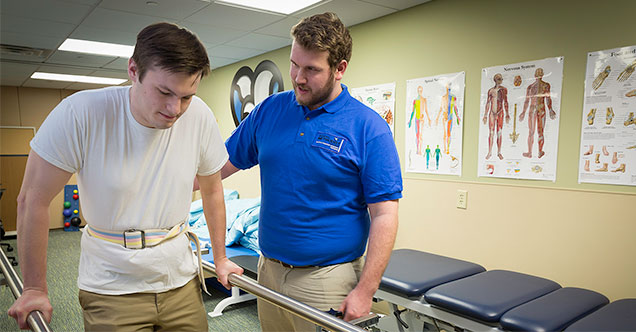 A physical therapist student practices hands-on at NMC's PTA lab.