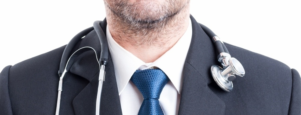 A man in a suit and tie with a stethoscope laid across his shoulders. There are many jobs available with a MBA in Healthcare.