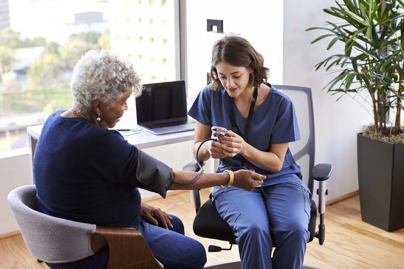 A medical assistant taking an elderly patient's blood pressure