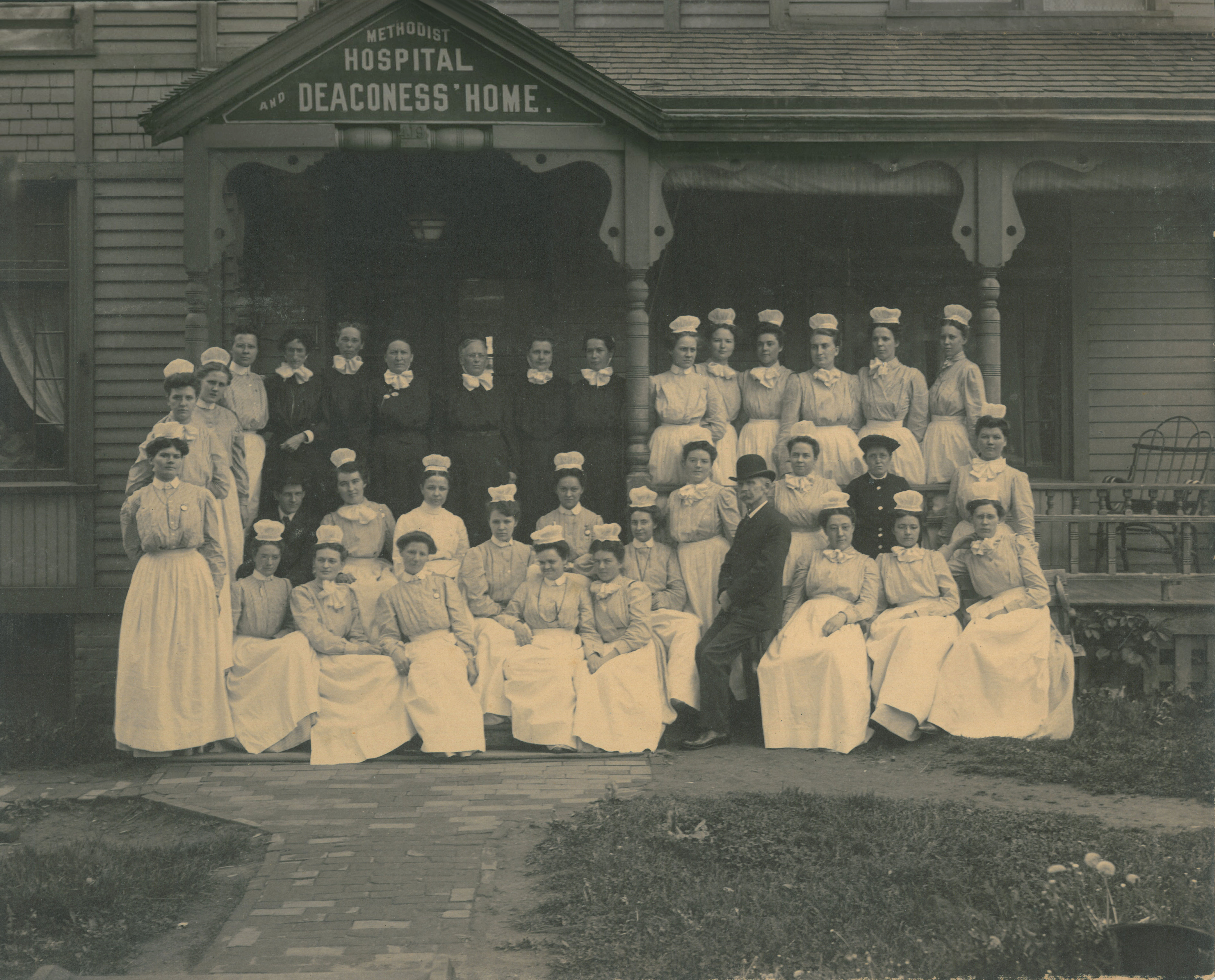 Black and white photo of one of the first classes of Nebraska Methodist College, set up in front of the Methodist Hospital and Deaconess' Home