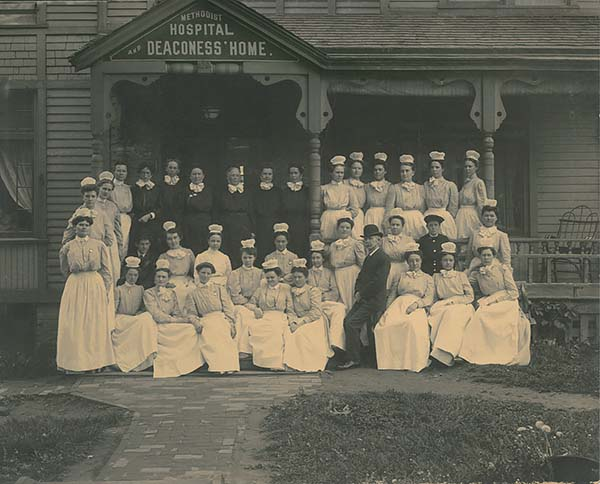 Sepia photo of deaconesses and nursing staff posed on steps of the Methodist Hospital and Deaconess' Home at 20th and Harney streets in Omaha.