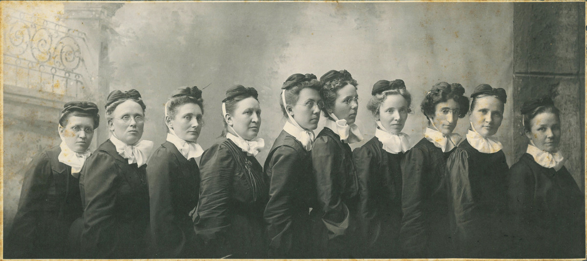 The first deaconesses who managed the original Nebraska Methodist Hospital  and its school of nursing. Photo of 10 women dressed in black uniforms with white collars - 1892 .