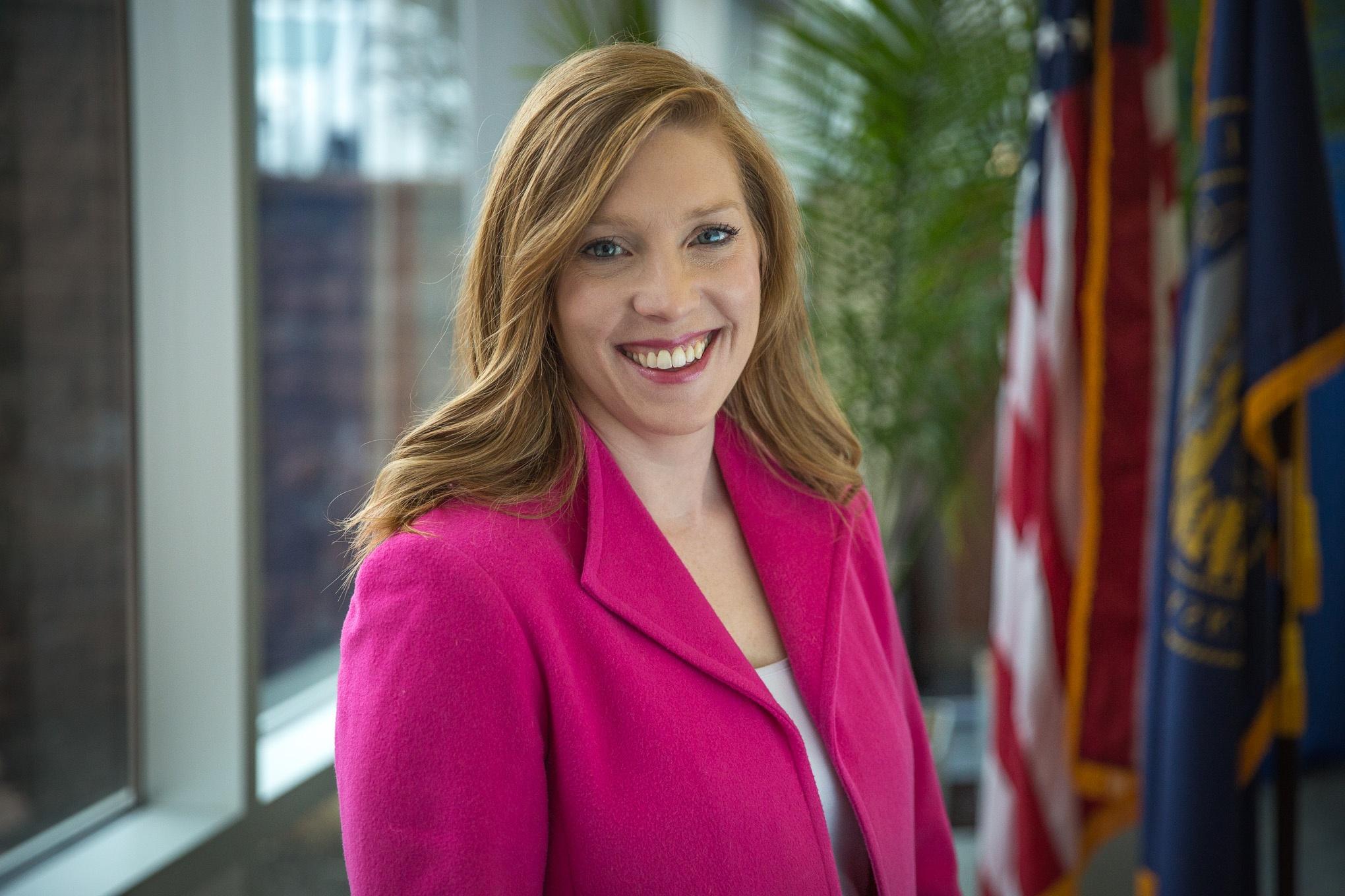 photo of NMC alum Anne Boatright beside U.S. and Nebraska flags.