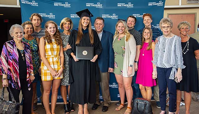 New NMC MOT graduate Megan Vermeer holding her diploma and surrounded by family members.