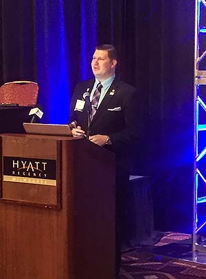AAMN President Blake Smith , an NMC alumnus, at the podium addressing the 2018 AAMN  Conference attendees.