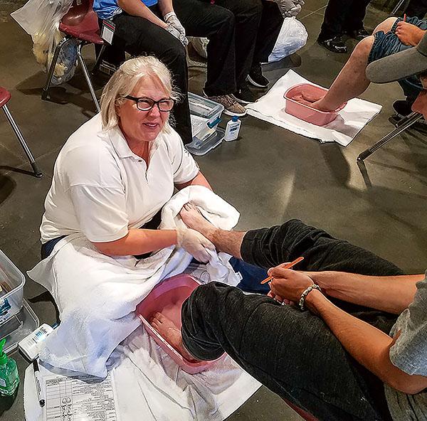 Lisa Kessler provides foot care at the Open Door Mission.