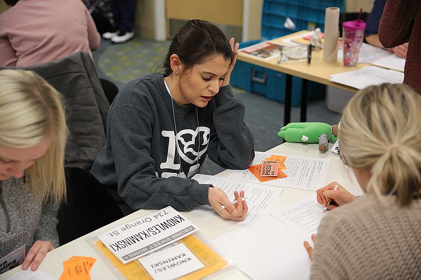 "A student fills out an application for benefits and assistance for her ""family"" during the poverty simulation."