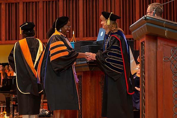 Image of Dr. Deb Carlson congratulating a DNP graduate.