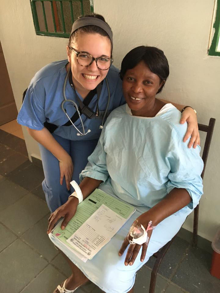 Alex Boulton, a sophomore nursing student at Nebraska Methodist College, poses with a Haitian woman after placing an IV in her hand.