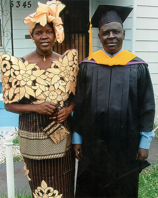 Anna Michael, poses in formal dress and headscarf, with husband, in graduation cap and gown, after he received his Master's degree from Bellevue University.