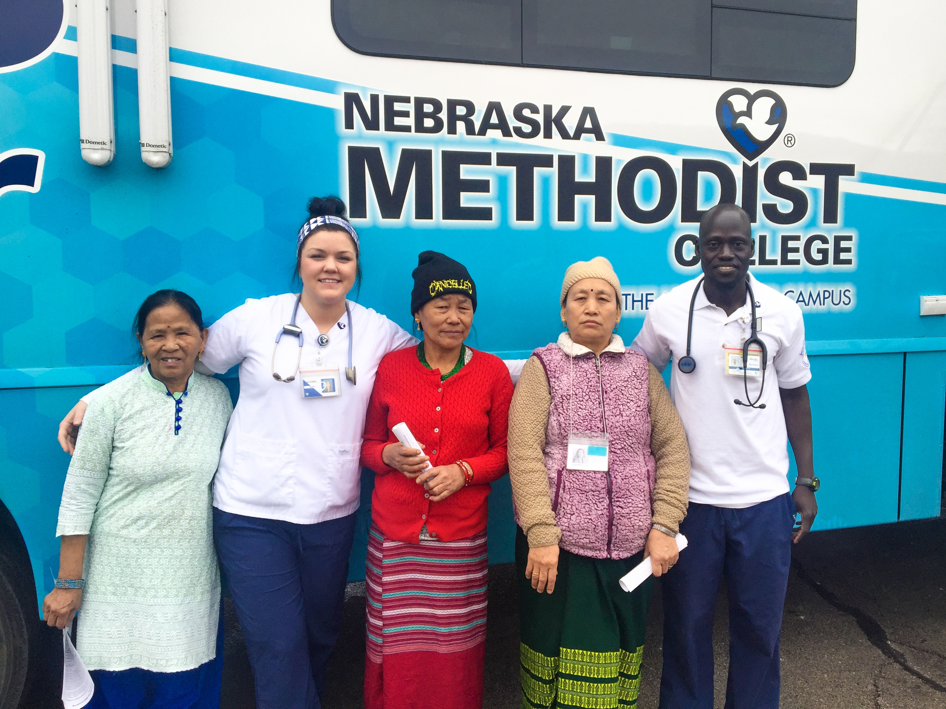 Image of Nebraska Methodist College nursing students and natives of Nepal outside NMC's Mobile Diabetes Center. As part of the college's community-based nursing and allied health curriculum, NMC nursing students and faculty provided diabetes screenings for elderly immigrants and refugees at Omaha's Intercultural Senior Center.