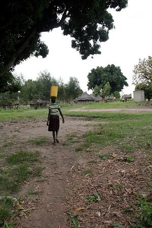 A villager carries water back to their home.