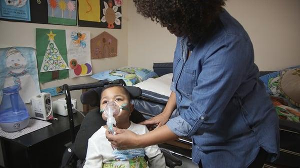 Latoya holding a respiratory mask on her son