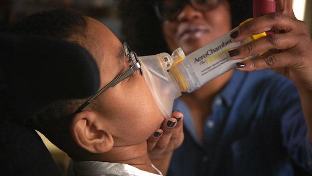 Respiratory therapist Latoya Sharp places mask on her son.