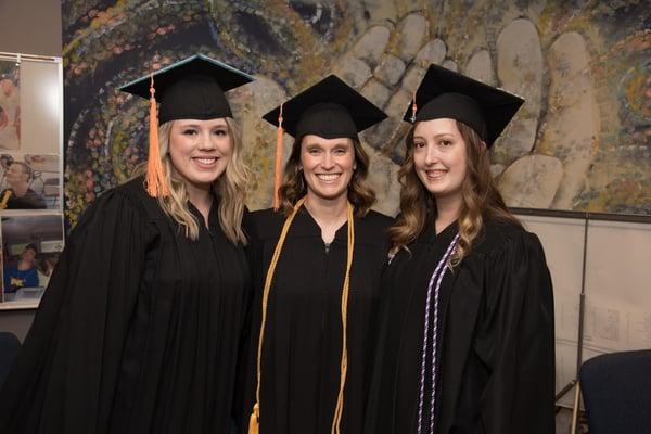 A trio of new graduates pose for a photo.