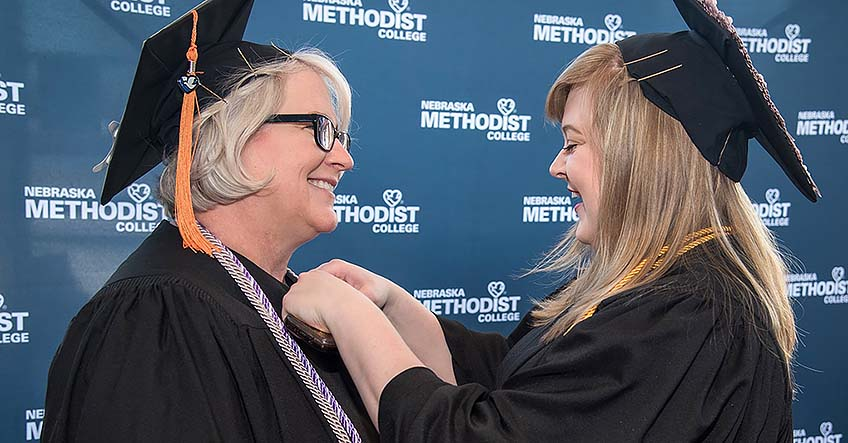 Lisa Kessler smiles as her daughter, Cassandra, helps adjust Lisa's graduation gown.