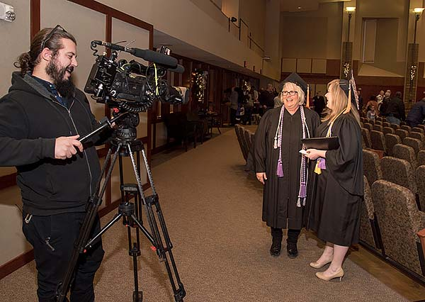 KMTV Channel 3 news reporter focuses videocamera on Lisa and Cassandra for a post-graduation interview.