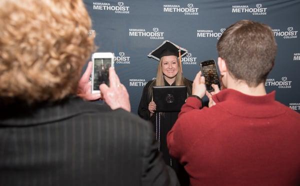 Proud family members take cell phone pics of their favorite graduate.