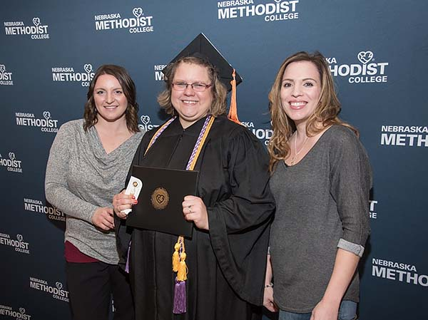 A proud new graduate poses with diploma and family.