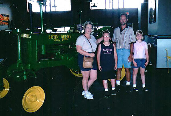 Family photo with mother Lisa and daughter Cassandra, as well as Cassandra's brother and father. All four of them are posing next to an old fashioned John Deere tractor