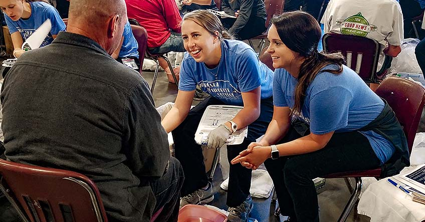 Master of Occupational Therapy students Jami Neckoliczak and Katelyn Leming provide a foot assessment  at the Foot Care Clinic for the Homeless held at Open Door Mission.