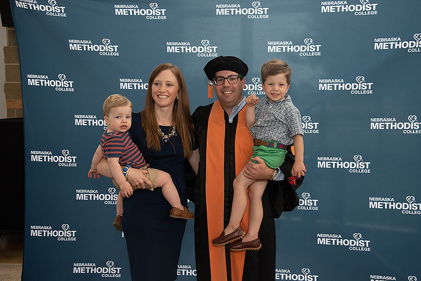 A new graduate poses for a photo with his family.