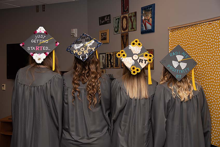 Graduates show off their decorated graduation caps.